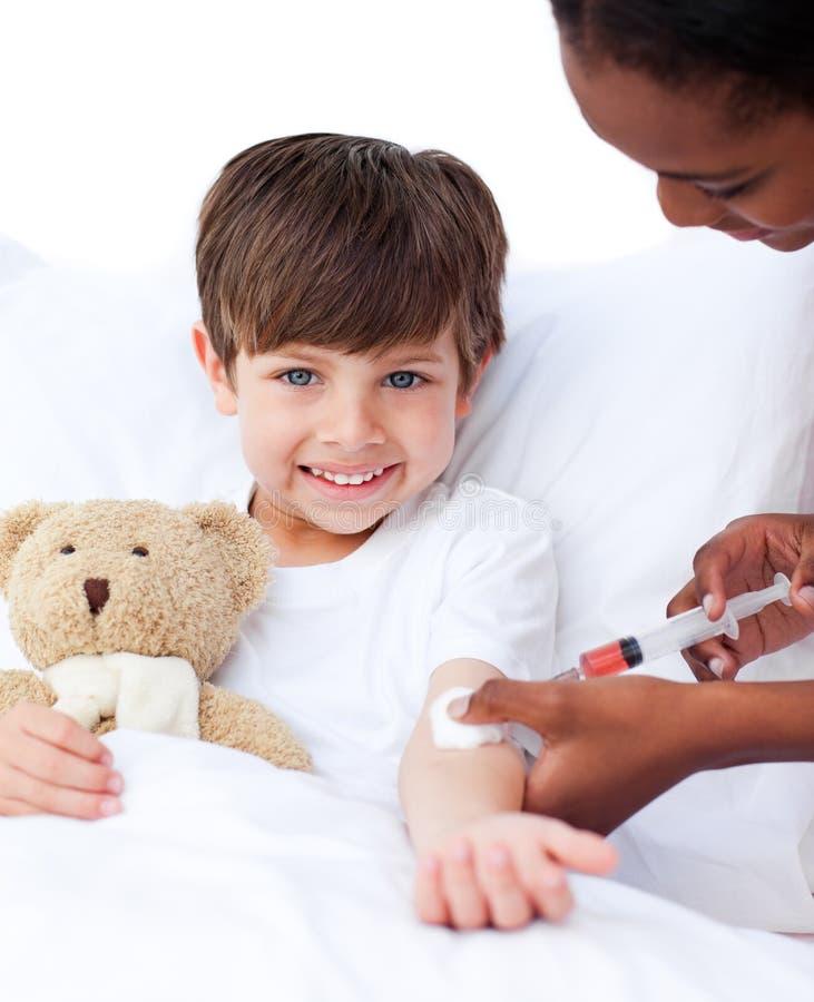 Χαμογελώντας μικρό παιδί που λαμβάνει μια έγχυση στοκ φωτογραφία