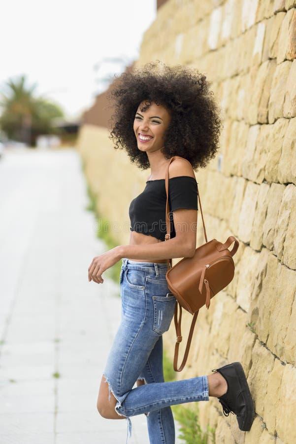 Χαμογελώντας μικτή γυναίκα με την τρίχα afro που στέκεται στην οδό στοκ εικόνες με δικαίωμα ελεύθερης χρήσης