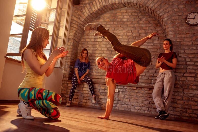 Χαμογελώντας μοντέρνος αρσενικός χορευτής σπασιμάτων που εκτελεί τις κινήσεις στοκ εικόνα