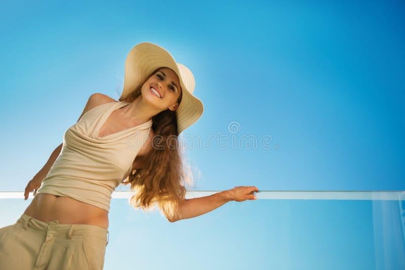 χαμογελώντας μόνιμη γυναίκα μπαλκονιών στοκ φωτογραφία