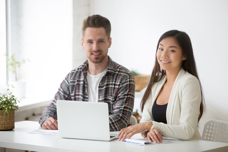 Χαμογελώντας νέα ασιατική επιχειρηματίας και ο καυκάσιος καθ. επιχειρηματιών στοκ εικόνες