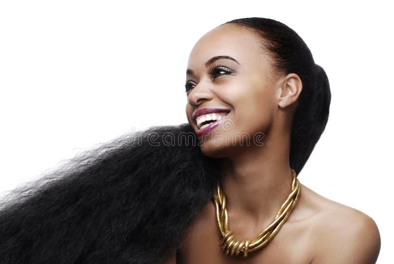 Χαμογελώντας νέα γυναίκα αφροαμερικάνων με την πολύ μακριά φυσική τρίχα στοκ φωτογραφία