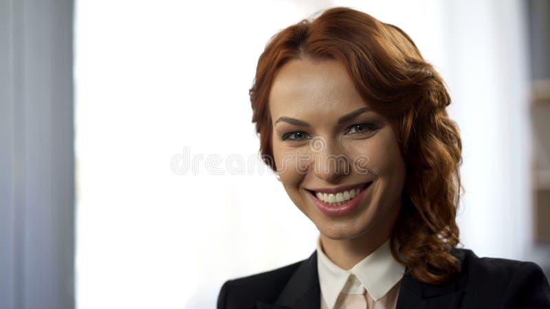 Χαμογελώντας νέα γυναίκα που εξετάζει τη κάμερα, κινηματογράφηση σε πρώτο πλάνο της επιτυχούς επιχειρησιακής κυρίας στοκ εικόνες