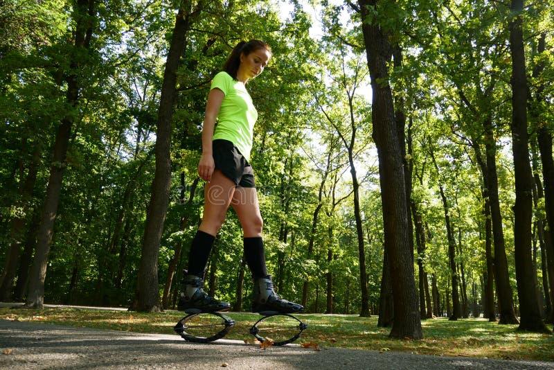 Χαμογελώντας νέα γυναίκα που κάνει τις ασκήσεις στα παπούτσια αλμάτων kangoo στοκ εικόνα