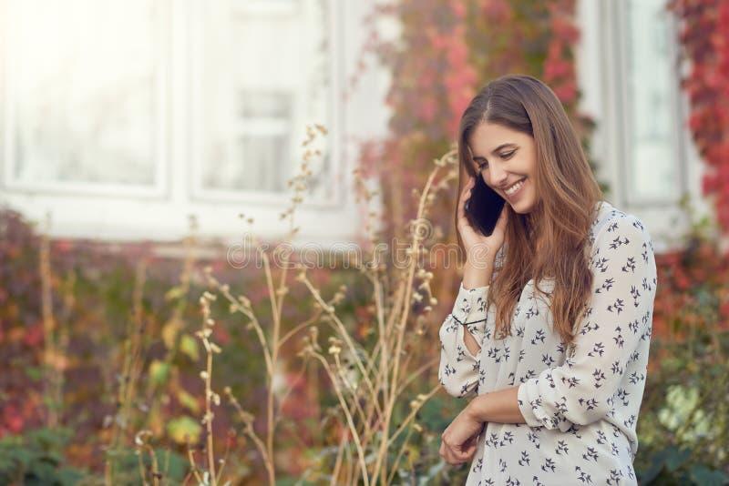 Χαμογελώντας νέα γυναίκα που κουβεντιάζει σε έναν κινητό στοκ φωτογραφία
