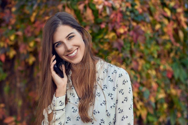 Χαμογελώντας νέα γυναίκα που κουβεντιάζει σε έναν κινητό στοκ φωτογραφίες