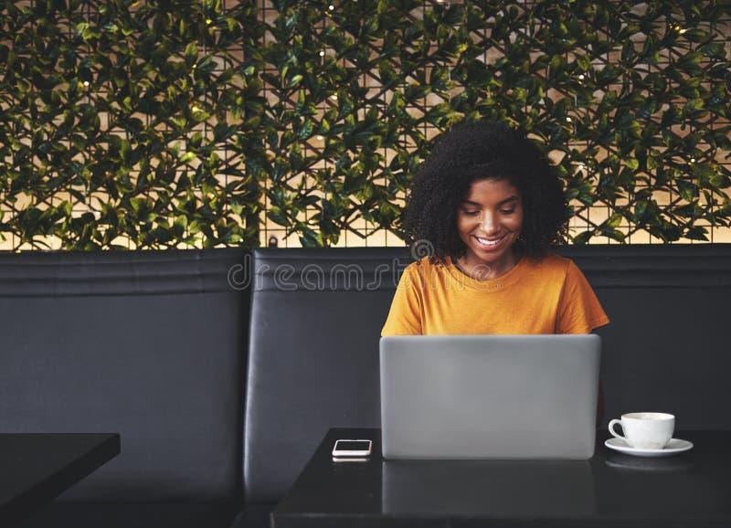 Χαμογελώντας νέα γυναίκα που χρησιμοποιεί το lap-top στον καφέ στοκ φωτογραφία