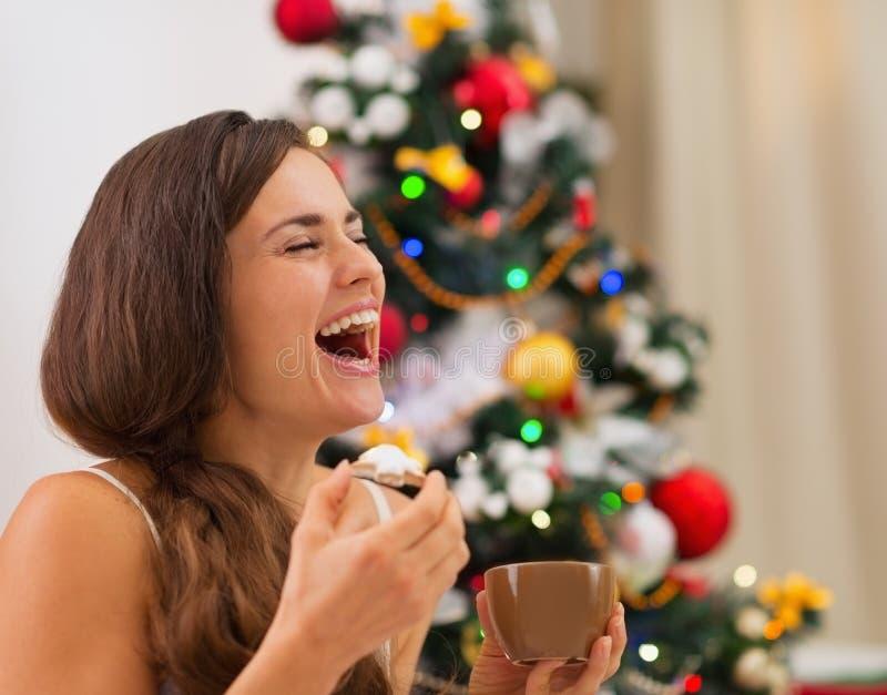 Χαμογελώντας νέα γυναίκα στις πυτζάμες που τρώει τα μπισκότα στοκ φωτογραφία με δικαίωμα ελεύθερης χρήσης