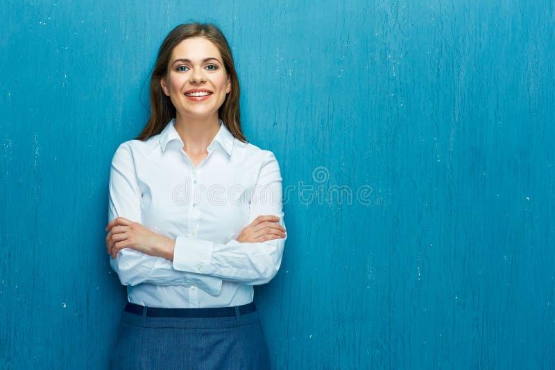 Χαμογελώντας νέα επιχειρησιακή γυναίκα ενάντια στον μπλε τοίχο στοκ εικόνα