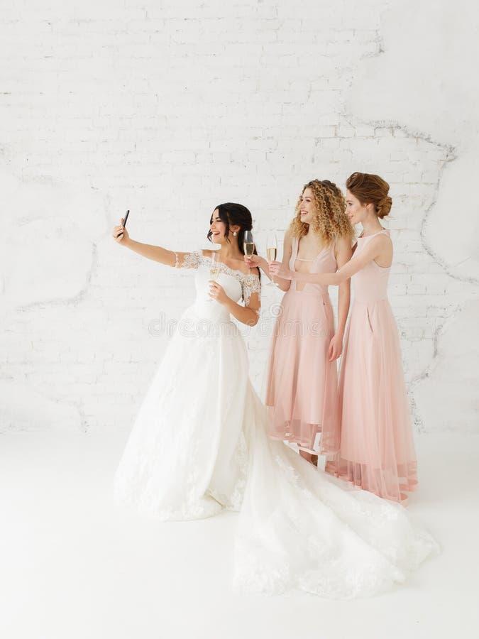 Χαμογελώντας νέα κορίτσια που παίρνουν ένα selfie από κοινού Νύφη και παράνυμφος που κάνουν τη φωτογραφία πρωινού στοκ φωτογραφία με δικαίωμα ελεύθερης χρήσης