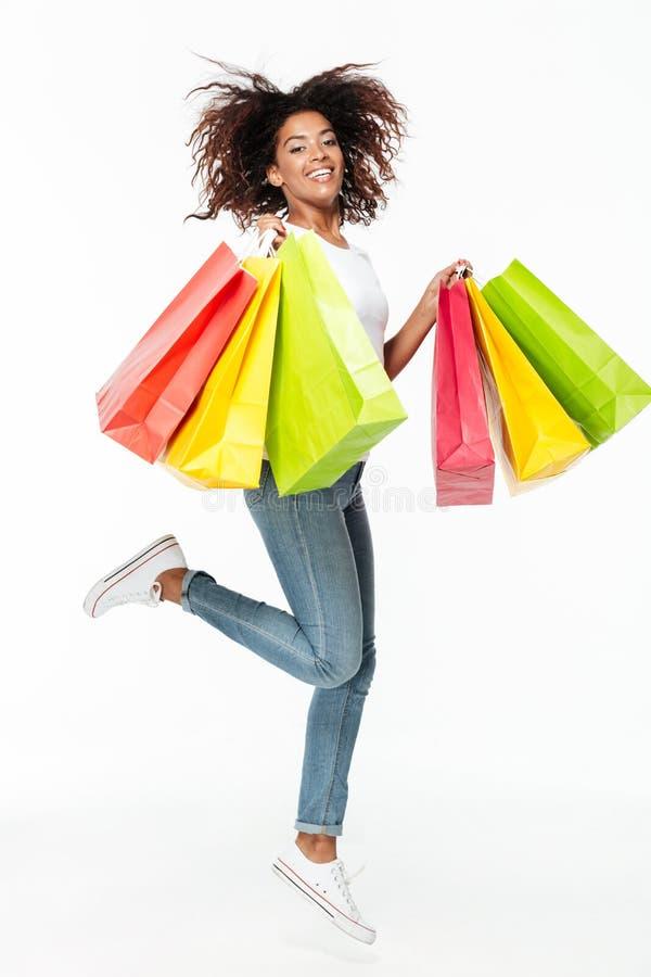 Χαμογελώντας νέες αφρικανικές τσάντες αγορών άλματος γυναικών στοκ φωτογραφία με δικαίωμα ελεύθερης χρήσης