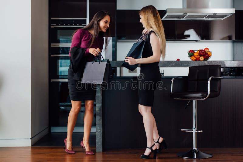 Χαμογελώντας νέες γυναίκες που φορούν τα επίσημα κομψά ενδύματα που εξετάζουν την τσάντα αγορών που στέκεται στο σύγχρονο διαμέρι στοκ εικόνα