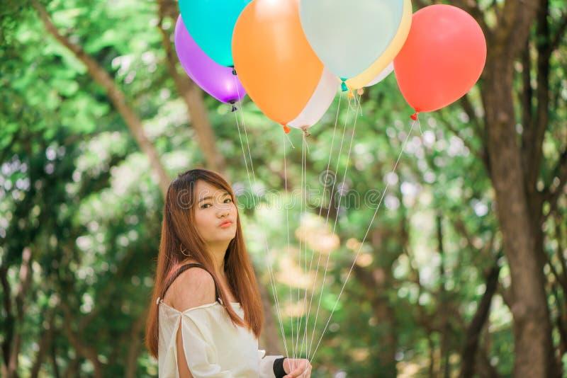 Χαμογελώντας νέες όμορφες ασιατικές γυναίκες με τη μακριά καφετιά τρίχα στο πάρκο Με τα τόξο-χρωματισμένα μπαλόνια αέρα στα χέρια στοκ εικόνες