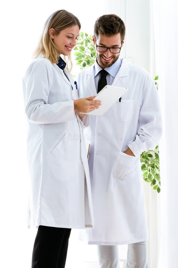 Χαμογελώντας νέοι γιατροί που φαίνονται ιατρικές εκθέσεις στην ψηφιακή ταμπλέτα στο ιατρικό γραφείο στοκ φωτογραφία