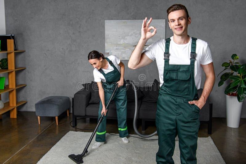 χαμογελώντας νέοι καθαρίζοντας εργαζόμενοι επιχείρησης που χρησιμοποιούν την ηλεκτρική σκούπα και την παρουσίαση εντάξει σημαδιού στοκ εικόνα