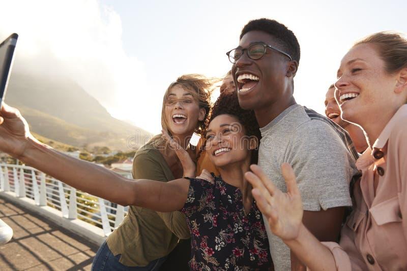 Χαμογελώντας νέοι φίλοι που θέτουν για Selfie στην υπαίθρια γέφυρα για πεζούς από κοινού στοκ φωτογραφίες με δικαίωμα ελεύθερης χρήσης