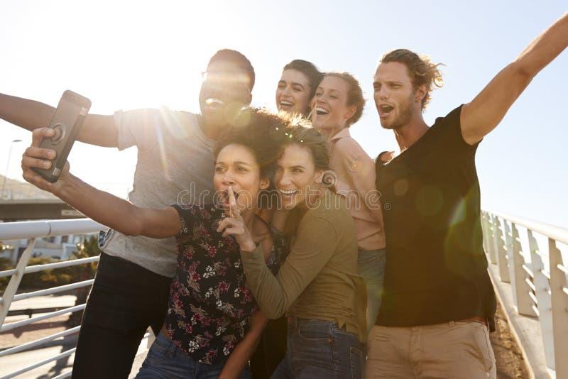 Χαμογελώντας νέοι φίλοι που θέτουν για Selfie στην υπαίθρια γέφυρα για πεζούς από κοινού στοκ φωτογραφία