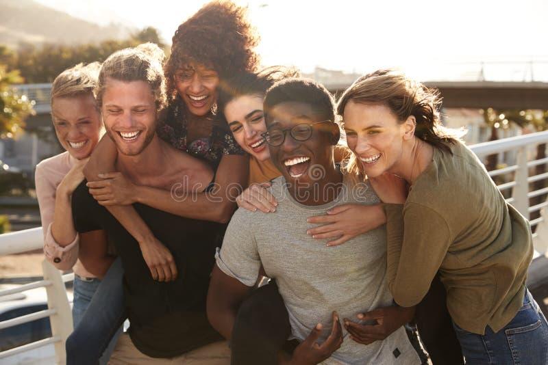 Χαμογελώντας νέοι φίλοι που περπατούν υπαίθρια από κοινού στοκ εικόνες