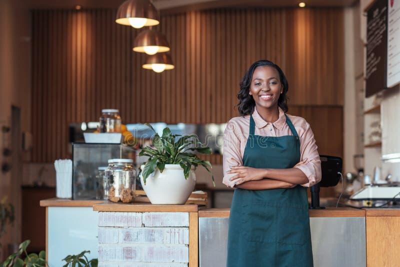 Χαμογελώντας νέος αφρικανικός επιχειρηματίας που στέκεται στον καφέ της στοκ εικόνες με δικαίωμα ελεύθερης χρήσης