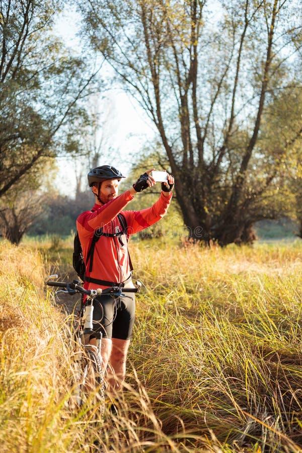 Χαμογελώντας νέος γενειοφόρος ποδηλάτης βουνών που παίρνει τις φωτογραφίες ενός όμορφου τοπίου στοκ εικόνες