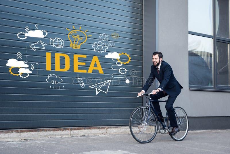 χαμογελώντας νέος επιχειρηματίας στο οδηγώντας ποδήλατο κοστουμιών στην οδό με τα εικονίδια επιγραφής και επιχειρήσεων ιδέας απεικόνιση αποθεμάτων