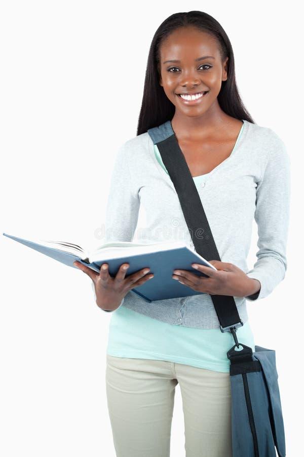 Χαμογελώντας νέος σπουδαστής με την ανάγνωση τσαντών στο βιβλίο της στοκ φωτογραφίες