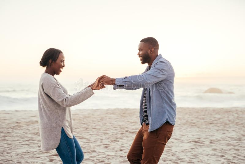 Χαμογελώντας νέο αφρικανικό ζεύγος που χορεύει σε μια παραλία στο ηλιοβασίλεμα στοκ εικόνα