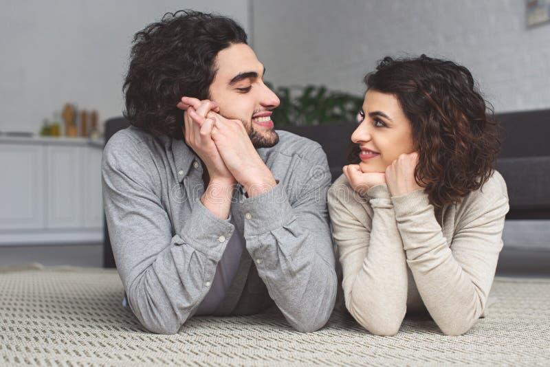 χαμογελώντας νέο ζεύγος που βρίσκεται στο πάτωμα και που εξετάζει το ένα το άλλο στοκ φωτογραφία