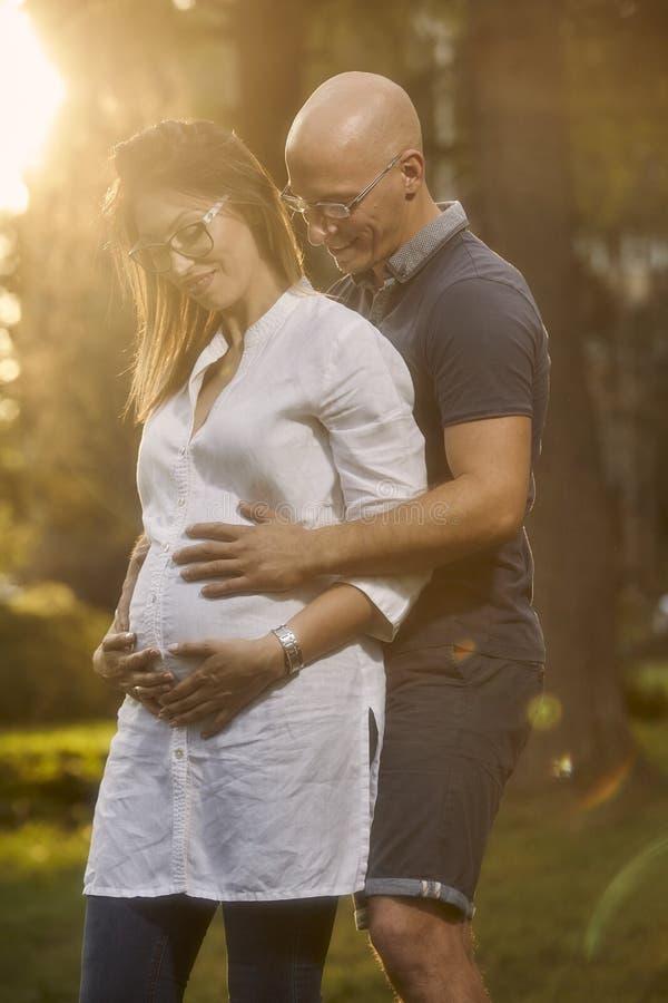 Χαμογελώντας νέο ζεύγος, που κρατά τα χέρια στο στομάχι εγκύων γυναικών στοκ φωτογραφία