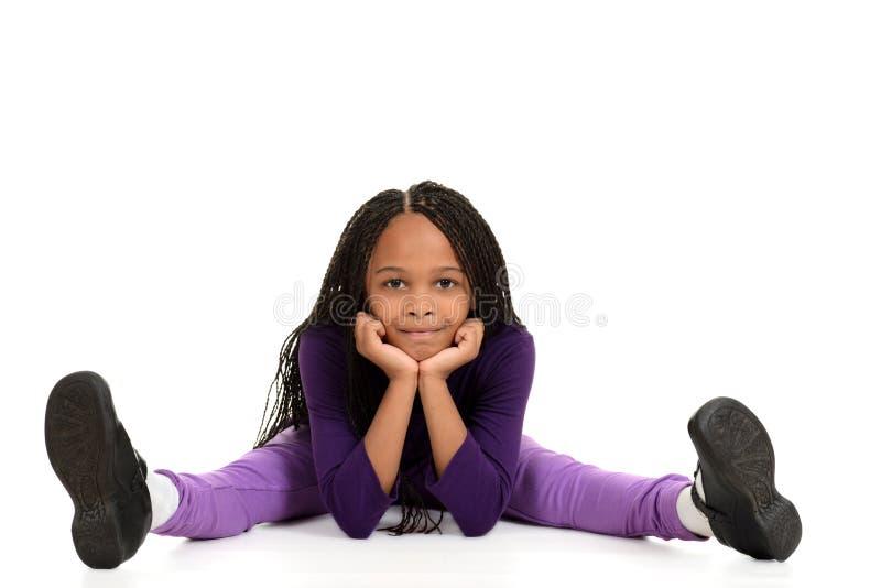 Χαμογελώντας νέο μαύρο κορίτσι που κλίνει στους αγκώνες στοκ φωτογραφίες