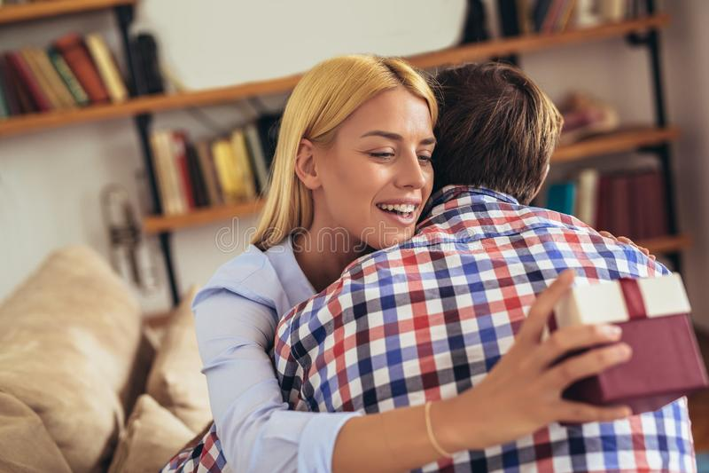 Χαμογελώντας νεαρός άνδρας που εκπλήσσει την εύθυμη γυναίκα με ένα κιβώτιο δώρων στοκ φωτογραφίες με δικαίωμα ελεύθερης χρήσης