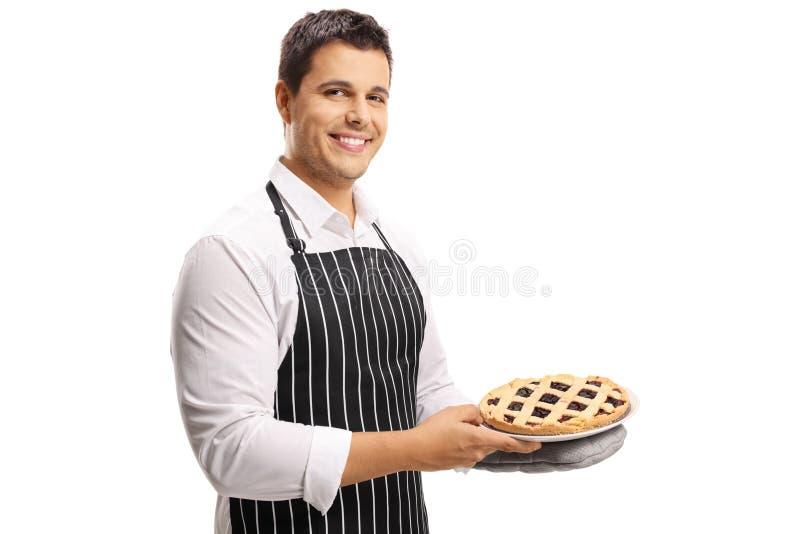 Χαμογελώντας νεαρός άνδρας που κρατά μια πίτα στοκ φωτογραφία με δικαίωμα ελεύθερης χρήσης