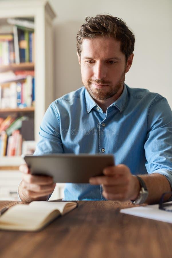 Χαμογελώντας νεαρός άνδρας που χρησιμοποιεί μια ταμπλέτα εργαζόμενος από το σπίτι στοκ φωτογραφία