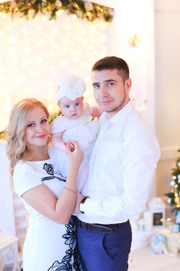 Χαμογελώντας ξανθοί μητέρα και πατέρας που κρατούν λίγο θηλυκό μωρό στο διακοσμημένο δωμάτιο για τα Χριστούγεννα στοκ εικόνα