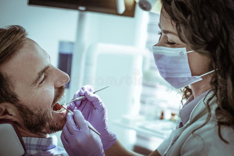 Χαμογελώντας οδοντίατρος που εξετάζει το χαμογελώντας ασθενή στοκ φωτογραφία με δικαίωμα ελεύθερης χρήσης