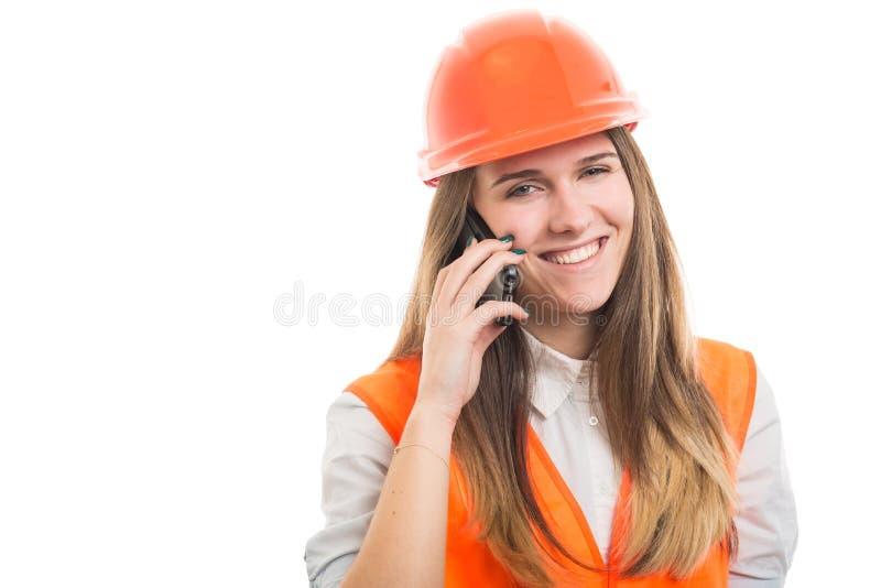 Χαμογελώντας οικοδόμος κοριτσιών που μιλά στο κινητό τηλέφωνο στοκ εικόνα με δικαίωμα ελεύθερης χρήσης