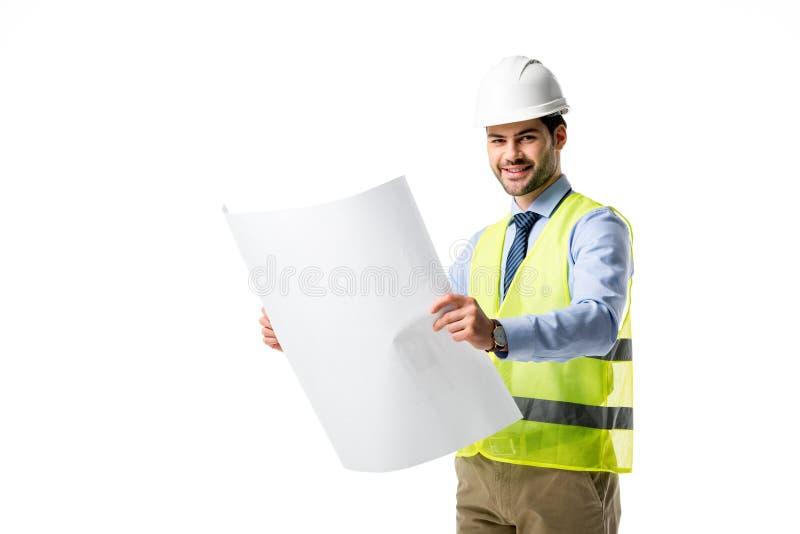 Χαμογελώντας οικοδόμος στην αντανακλαστική φανέλλα και hardhat που εξετάζει το σχεδιάγραμμα στοκ φωτογραφία με δικαίωμα ελεύθερης χρήσης