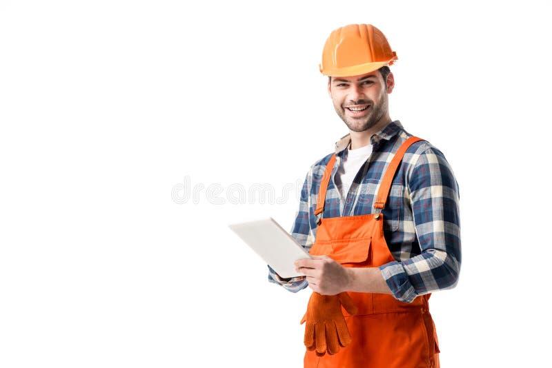 Χαμογελώντας οικοδόμος στο πορτοκαλί γενικό και σκληρό καπέλο που χρησιμοποιεί την ψηφιακή ταμπλέτα στοκ εικόνες με δικαίωμα ελεύθερης χρήσης