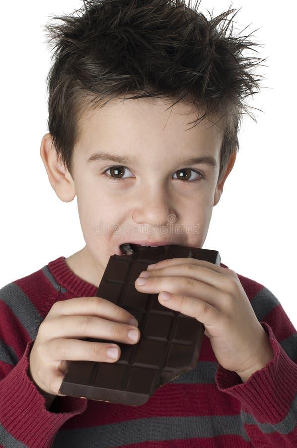 Χαμογελώντας παιδί που τρώει τη σοκολάτα στοκ φωτογραφίες με δικαίωμα ελεύθερης χρήσης