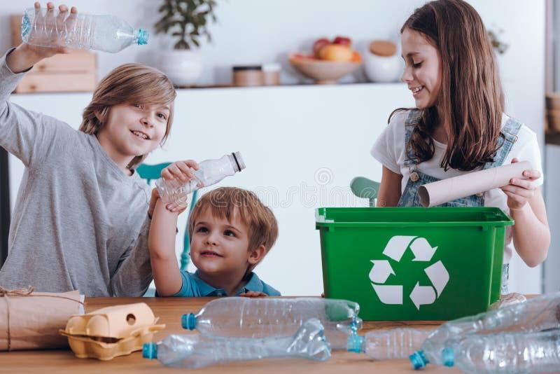 Χαμογελώντας παιδιά που διαχωρίζουν τα πλαστικά μπουκάλια στοκ εικόνα