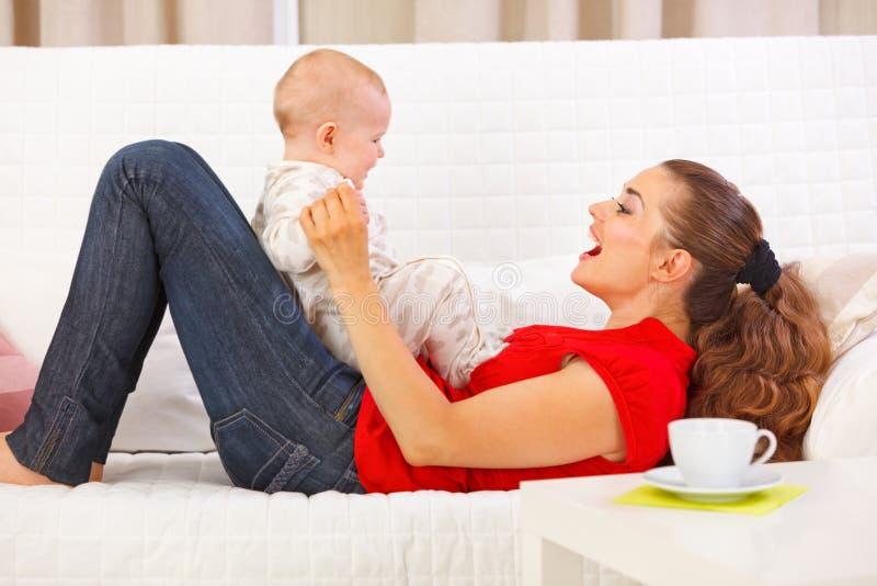Χαμογελώντας παιχνίδι μητέρων και μωρών στο ντιβάνι στοκ φωτογραφίες με δικαίωμα ελεύθερης χρήσης