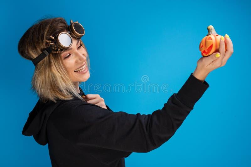 Χαμογελώντας πανκ κορίτσι ατμού που κρατά μια χαρασμένη πορτοκαλιά μικρή κολοκύθα στοκ εικόνες