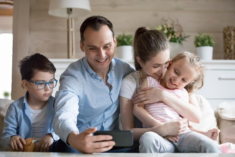 Χαμογελώντας πατέρας που κάνει selfie της ευτυχούς τετραμελούς οικογένειας στοκ φωτογραφία
