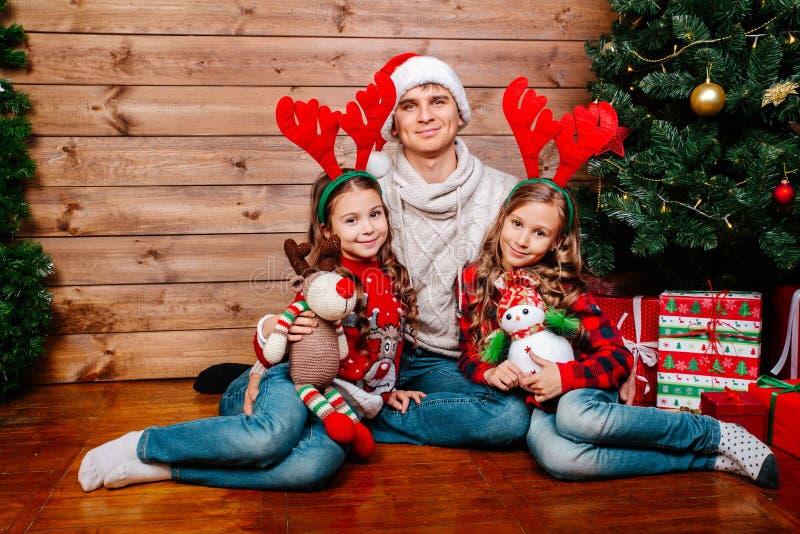 Χαμογελώντας πατέρας στο καπέλο santa και κόρη που αγκαλιάζει και που κρατά το κιβώτιο δώρων κοντά στο χριστουγεννιάτικο δέντρο σ στοκ φωτογραφίες με δικαίωμα ελεύθερης χρήσης