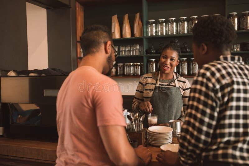 Χαμογελώντας πελάτες που διατάζουν τον καφέ από ένα barista καφέδων στοκ εικόνα με δικαίωμα ελεύθερης χρήσης