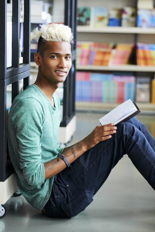 Χαμογελώντας περίεργος σπουδαστής στην πανεπιστημιακή βιβλιοθήκη στοκ εικόνα με δικαίωμα ελεύθερης χρήσης