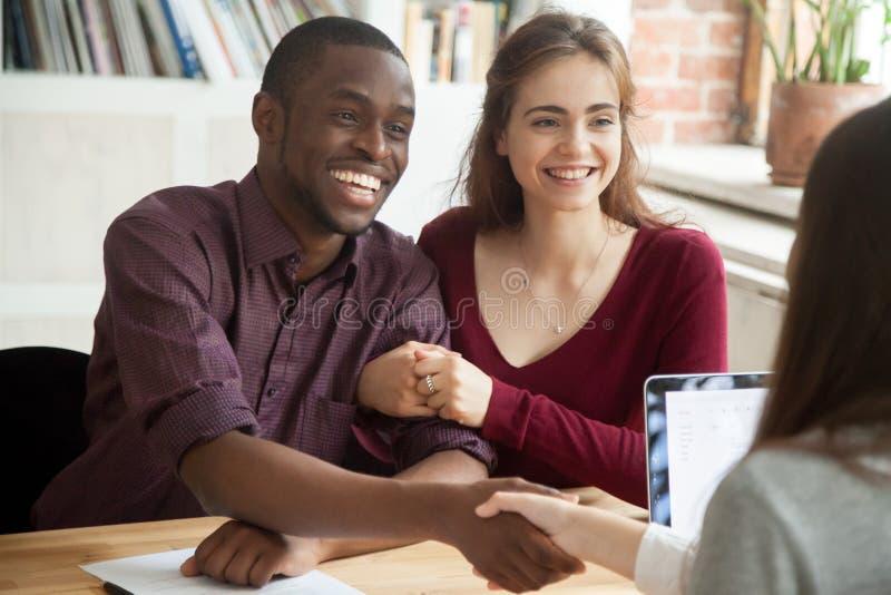 Χαμογελώντας πολυφυλετικοί πελάτες ζευγών που τινάζουν τα χέρια με το μεσίτη ο στοκ εικόνα