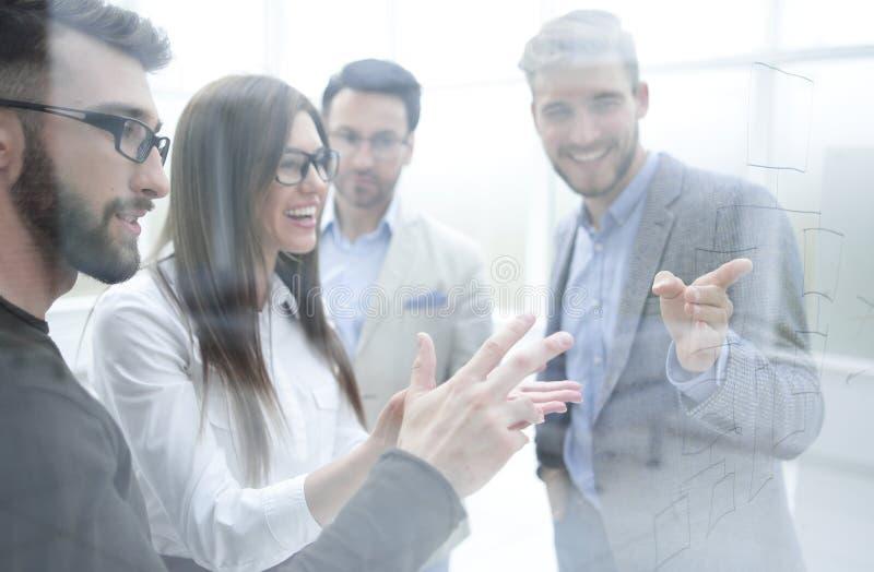 Χαμογελώντας προσωπικό που συζητά κάτι που στέκεται στο γραφείο στοκ εικόνα με δικαίωμα ελεύθερης χρήσης