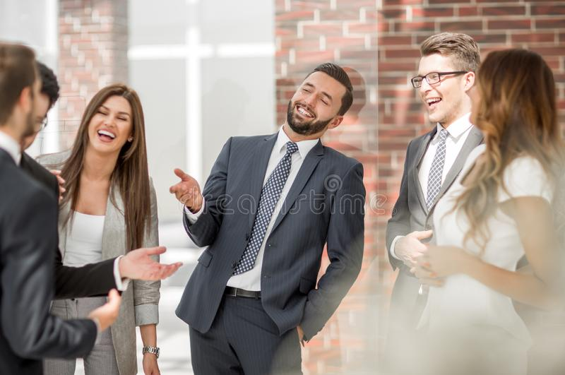 Χαμογελώντας προσωπικό που συζητά κάτι στο διάδρομο γραφείων στοκ εικόνες