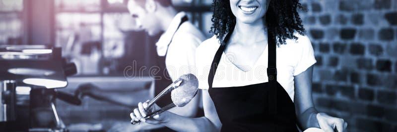 Χαμογελώντας σερβιτόρα που βάζει το ρόλο ψωμιού στην τσάντα εγγράφου στοκ εικόνες